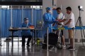 Airport security staff check the temperature of passengers at Beijing Capital International Airport. Photo: EPA-EFE