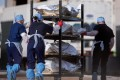 El Paso County Medical Examiner's Office staff in Texas move bodies that are in bags labelled 'Covid' from refrigerated trailers into a morgue. Photo: Reuters