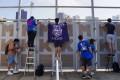 Fans climb fences to watch Hong Kong football matches that were played behind closed doors. Photo: Sam Tsang