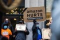 Demonstrators hold signs during a protest outside the home of Amazon chief executive Jeff Bezos in New York on Wednesday. Photo: Bloomberg