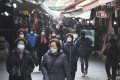 People walk through a market in Seoul, South Korea, as people are urged to stay home while the country's coronavirus infections continue to soar. Photo: AP