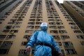 A security guard in protective gear stands outside Kwai Shing West Estate in Kwai Chung. Photo: Winson Wong