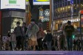People wearing masks cross the street in Tokyo earlier this month. Photo: AP