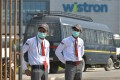 Private security guards stand at the entrance of the Taiwanese-run iPhone factory at Narsapura on Sunday. Photo: AFP