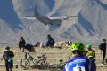 An Indian Air Force aircraft flies past cyclists near a mountain range in Leh, the joint capital of the union territory of Ladakh bordering China. Photo: AFP