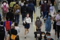 A woman wearing a facemask runs past other commuters walking in an MTR underground metro station. Photo: AFP