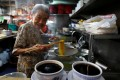 Hawker Leong Yuet Meng of Nam Seng Noodle House cooks at her shop in Singapore in February 2019. Photo: Reuters