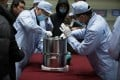 Scientific researchers transfer a container loaded with moon samples retrieved by the Chang'e-5 probe. Photo: Xinhua