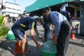 Staff members deliver drinking water to people living in the lockdown area near a seafood market in Samut Sakhon, Thailand on Saturday. Photo: Xinhua
