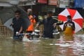 People wade through a flooded street following heavy monsoon rains in Mumbai on September 23. Photo: AFP
