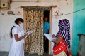 Health workers conduct a door-to-door survey for the first shot of Covid-19 vaccine for people older than 50 years and with co-morbidities in a village on the outskirts of Ahmedabad, India, on December 14. Photo: Reuters