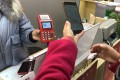 Li Lan, who won a 200-yuan red packet in Suzhou's e-yuan test, scans a QR code with her smartphone to make a payment at an electronics shop. Photo: Orange Wang