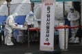 Medical workers wearing protective gears prepare to take sample at a coronavirus testing site in Seoul, South Korea. Photo: AP