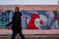 A man wearing a face mask walks past a mural in Berlin featuring a likeness of Santa Claus holding a coronavirus. Photo: AFP