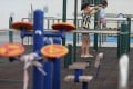 A mother holds her child's hands as he walks across a beam at a playground in Aberdeen on June 22. Photo: Nora Tam