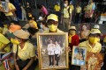 Well-wishers hold the portraits of Thai King Maha Vajiralongkorn and Queen Suthida, as they attend a ceremony to mark King Taksin Memorial Day in Bangkok on December 28. The moral authority of the monarchy is deeply recognised and revered in Thailand. Photo: EPA-EFE