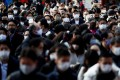 Visitors wearing face masks wait to offer prayers at a shrine in Tokyo on Monday. Japan saw a spike in coronavirus cases over the year-end period. Photo: Reuters