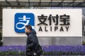 A pedestrian walks past an Alipay sign in Shanghai in December. Photo: Bloomberg