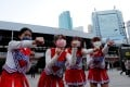 Cheerleaders perform in front of Shimbashi Station during the rush-hour in Tokyo on Thursday. Photo: Reuters