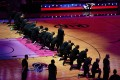 Miami Heat forward Meyers Leonard stands while teammates kneel during the playing of the national anthem prior to the game against the Boston Celtics. Photo: USA Today