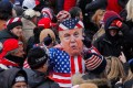A person in a Donald Trump mask gestures as the US president's supporters gather in Washington on Wednesday. Photo: Reuters