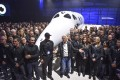 Virgin Galactic's Richard Branson (front, centre) gathers with Virgin Galactic employees in front of the SpaceShip Two VSS Unity after a roll-out ceremony. The company is set to begin commercial space flights this year. Photo: Getty Images
