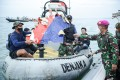 Indonesian Navy personnel transport debris believed to be from the Sriwijaya Air SJ-182 jet. Photo: Antara Foto via Reuters