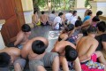 Chinese nationals sit with their hands bound after being arrested by Cambodian police in 2011 on suspicion of extorting money from victims abroad. Photo: AFP
