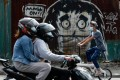 People ride past a mural reminding residents in Manila to wear face masks. Photo: Reuters