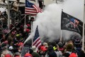 A supporter of US President Donald Trump sprays smoke during a protest outside the Capitol building in Washington on January 6. Photo: Reuters