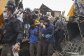 Rescuers evacuate a quake survivor pulled out from the ruin of a collapsed building in Mamuju, Indonesia. Photo: EPA-EFE