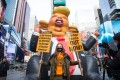 A protester poses with posters next to a Donald Trump Rat Balloon created by local artists during a demonstration in Times Square, New York on January 9. Photo: AFP