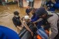 Rescuers assist an elderly man onto their boat in Banjarmasin, South Kalimantan. Photo: AP