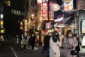 People wearing face masks walk on a street filled with restaurants and bars during a coronavirus state of emergency in Tokyo on Thursday. Photo: AP