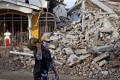 A man walks past a house that collapsed in Friday's earthquake in Mamuju, West Sulawesi. Photo: AP