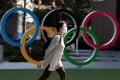 A woman walks past the Olympic rings in front of the Japan Olympics Museum, in Tokyo, in March 2020. Photo: Reuters