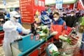 A worker in protective suit serves customers at a supermarket checkout counter in Wuhan in February 2020, amid the coronavirus outbreak. Photo: China Daily via Reuters