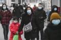 People wearing face masks walk in Beijing on Wednesday. Photo: Kyodo