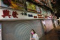 A woman in a mask walks past a row of closed shops on Ashley Road in Hong Kong's Tsim Sha Tsui. Photo: Nora Tam
