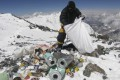 A Nepalese sherpa collects garbage left by climbers at an altitude of 8,000 metres during a Mount Everest clean-up expedition. A local group plans to create art out of some of the waste left at the world's highest peak. Photo: AFP