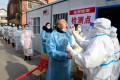 """Residents receive coronavirus tests at a residential compound in Shijiazhuang, Hebei province, as part of a mass testing programme after the province declared an """"emergency state"""" this month. Photo: AFP"""