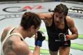 Julianna Pena punches Sara McMann in their bantamweight fight at UFC 257. Photos: Jeff Bottari/Zuffa LLC