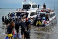 Tourists preparing to board a fast boat from Sanur beach, on the Indonesian resort island of Bali, this month. Some visitors obtain visas under false pretences and breach their conditions by working while there, as the recent expulsions of American Kristen Gray and Russian Sergei Kosenko have revealed. Photo: AFP