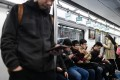 Commuters use their phones on a subway in Beijing on April 8, 2019. Photo: AFP