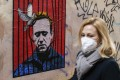A woman in Rome walks by a poster depicting Alexei Navalny behind bars with a dove freeing him from detention. Photo: EPA-EFE