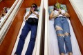 Devotees lie down and pray inside coffins to 'trick death and improve their luck' at a temple in Bangkok. Photo: Reuters