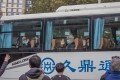 WHO experts leave the Jade Boutique Hotel in Wuhan by bus on Thursday after spending 14 days in quarantine. Photo: EPA-EFE