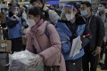 Staff wearing face masks and shields direct rail passengers in Beijing on Thursday, although the number travelling was said to be smaller than in previous years. Photo: AP