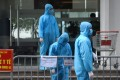 Medical workers in protective suits stand outside a quarantined building amid the coronavirus outbreak in Hanoi. Photo: Reuters