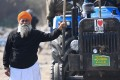 A farmer stands next to his tractor during an ongoing protest against the central government's recent agricultural reforms. Photo: AFP